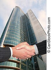 Business handshake on modern city background