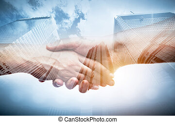 Business handshake over modern downtown skyscrapers, double exposure. Concepts of financial deal, agreement.