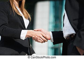 Business handshake - corporate man and woman