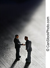business handshake on a Newspaper with Financial numbers