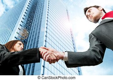 Business handshake against modern offices