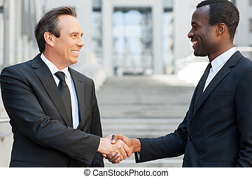 Business handshake. Two cheerful business men shaking hands while standing outdoors