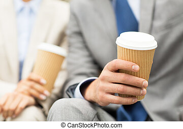 close up of business people hands with coffee cups