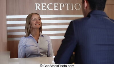 Close up of stunning receptionist greeting hotel guest, checking his passport and making a call to check if the room is ready