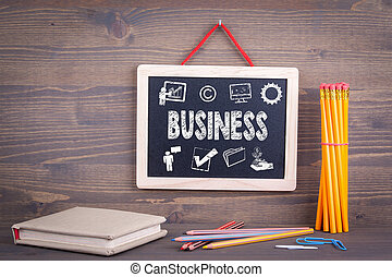 Business icon concept. Chalkboard on a wooden background