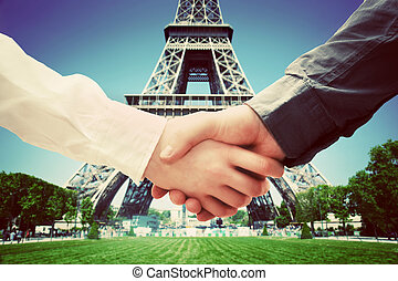 Business in Paris, France. Handshake on Eiffel Tower background. Deal, success, contract, cooperation concepts