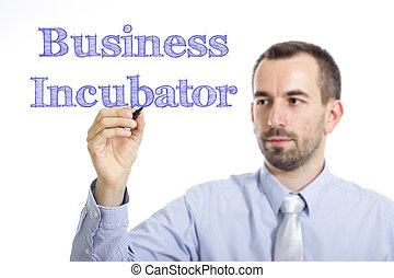 Business Incubator - Young businessman writing blue text on transparent surface