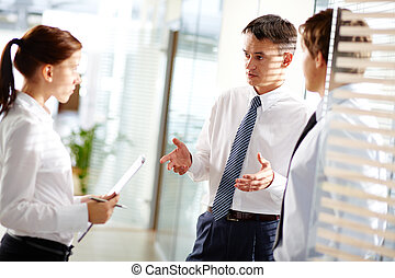 Business interaction - Mature businessman addressing his...