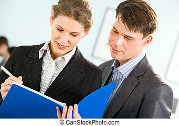 Portrait of business woman and man reading a document