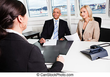 Business Interview - Three businesspeople at an interview in...