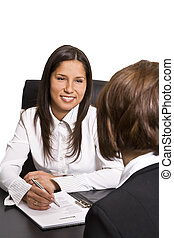 Two businesswomen at an interview in an office. The documents on the desk are mine.
