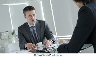 Business issues - Handsome businessman telling his colleague...