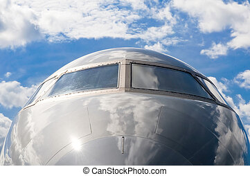 business jet cockpit abstract against a cloudy blue sky