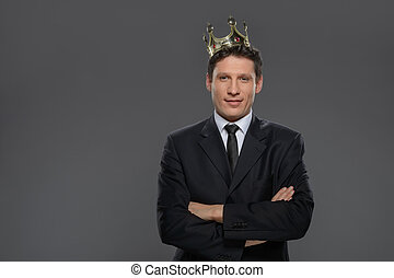 Business king. Confident businessman in crown standing isolated on gray with his arms crossed