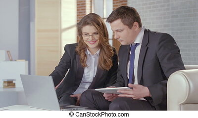 Business lady and man check presentation on laptop, slow motion