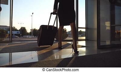Business lady going to the airport with her luggage. Young woman in heels entering walking through glass doors to the terminal and roll suitcase on wheels. Trip or vacation travel concept. Slow motion