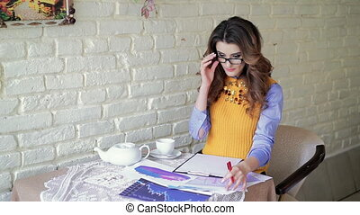 Business lady in glasses working with documents in cafe