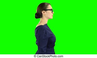 Business lady is walking and waving to her friends. Green...