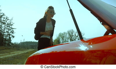 lady looks under the hood of the car outdoors