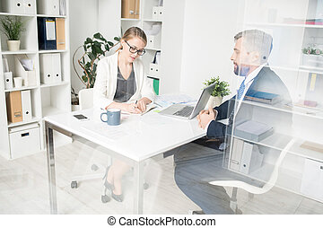 Business lady making notes while talking to subordinate