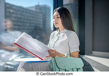 Pretty young dark-haired businesswoman looking serious and looking through the documents