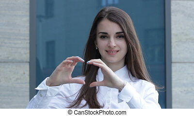 business Lady shows hands symbol of the heart and smiling