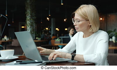 Business lady using laptop in restaurant typing sitting at ...
