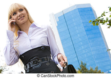 Business lady - View from below of smart woman talking on...