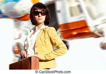 Elegant business lady with case and flying helicopter