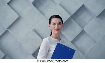 Business lady with clipboard posing for camera
