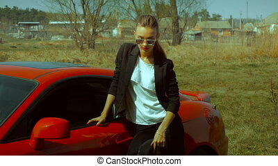 business lady with red lips posing near a sport car