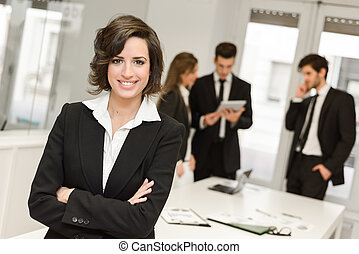 Business leader looking at camera in working environment - ...