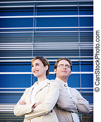 Business leadership - Business man and woman standing side...