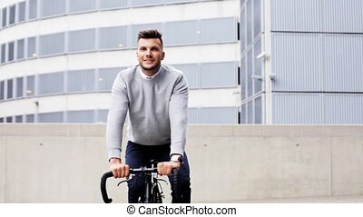 young man riding bicycle on city street - business,...