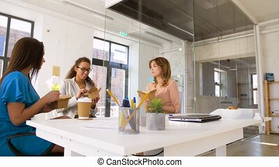 happy businesswomen eating take out food at office -...
