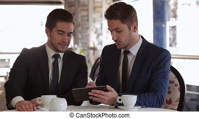 Men use the tablet at lunchtime - Business lunch in a...