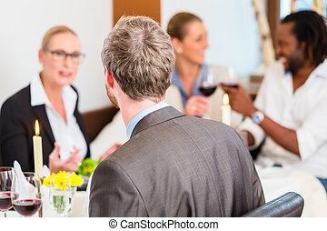 Business lunch in restaurant with food and wine