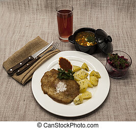 Business lunch : Petite Wiener schnitzel with boiled potatoes and ketchup. Served on a white porcelain plate with fork and knife on a wooden background. Beet salad and tomato, red pepper soup, sauce with olive oil, rosemary and smoked paprika with fork and a glass of juice and knife on a wooden background