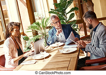 Business lunch. Three people in the restaurant sitting at table brainstorming on project using digital devices. Team work concept