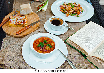 Business lunch with soup, salad and coffee served at the table in the restaurant. On the cloth lay the glasses and the book