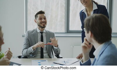 Business male and female colleagues laughing while talking...