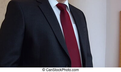 business man adjusts his suit and other men's accessories