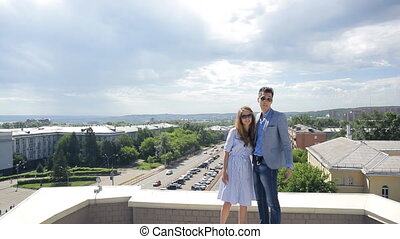 Business man and woman are standing on roof posing.