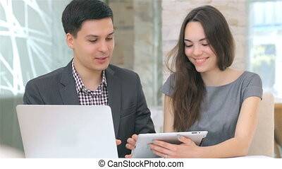 Business man and woman discussing collating data on the tablet