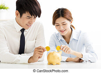 business man and woman putting coin into  piggy bank