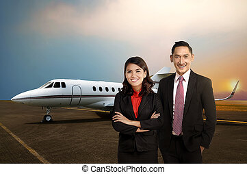 Business man and woman smiling in front of private jet