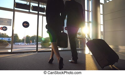 Business man and woman with luggage going from the airport to city street. Follow to young businessman carrying suitcase on wheels and walking with his female colleague from terminal hall. Slow motion