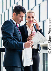 Business man and woman with paper and phone
