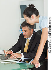 Business man and woman working on a laptop