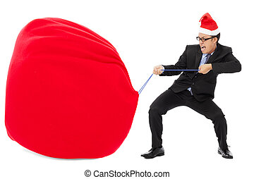 business man carrying a heavy gift sack with christmas hat